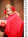 Girl in autumn park enjoying hot drink 54753147