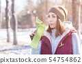 Portrait of a sports girl engaged in a workout in the winter on an outdoor sports field. Drinks 54754862