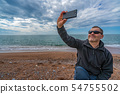 Man with sunglasses taking selfie on the beach 54755502
