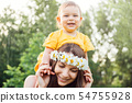 Mother giving piggyback ride to her loving daughter outside in nature. Hippie mother and happy baby 54755928