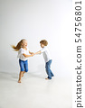 Boy and girl playing together on white studio background 54756801