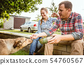 Young and happy farmer's couple at their garden in sunny day 54760567