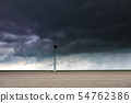 dark stormy sky over plowed field and wind turbine 54762386