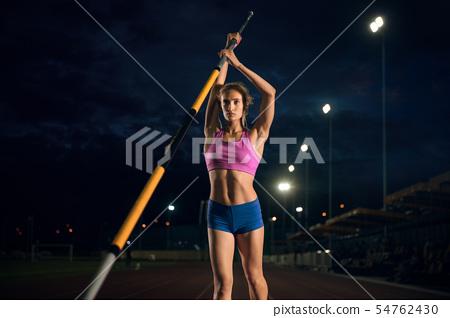 Female pole vaulter training at the stadium in the evening 54762430
