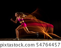 Professional female relay racer training on black studio background in mixed light 54764457