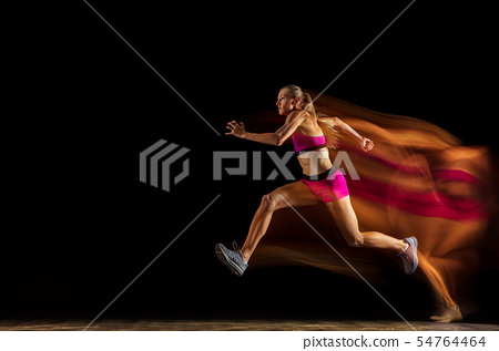 Professional female relay racer training on black studio background in mixed light 54764464