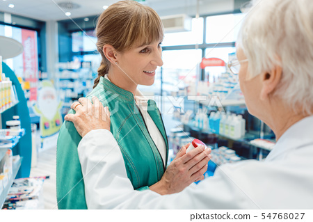 Woman customer in pharmacy buying drug hoping to get better 54768027