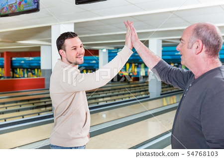 Smiling father and son giving high-five 54768103