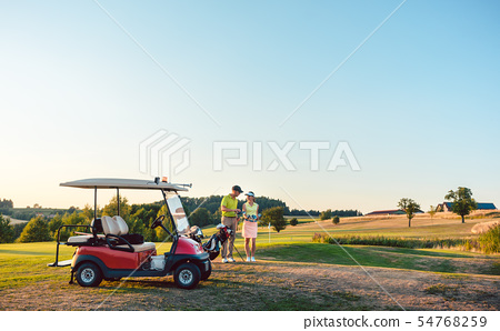 Woman and her partner or instructor holding various golf clubs near golf cart 54768259