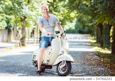 Young man riding old scooter 54768281