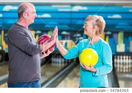 Smiling mature couple giving high-five 54768303