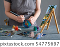 Painter painting with stained glass paints on vase 54775697