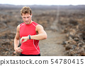 Running athlete man looking at heart rate monitor 54780415