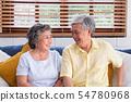 Asian senior couple sitting and embracing at sofa 54780968
