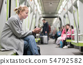 Beautiful blonde woman wearing winter coat reading on the phone while traveling by metro public 54792582