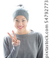 Close up portrait of cheerful caucasian woman, gesturing peace sign and smiles 54792773