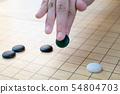 black stone in hand playing weiqi, igo, baduk game 54804703