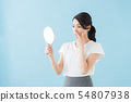 Woman looking at a mirror (blue background) 54807938