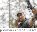 Man hunts in the forest with a bow. The hunter aims. 54808321