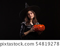 Little girl with a serious expression making a spell while holding a pumpking for halloween 54819278