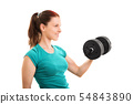 Smiling fit girl lifting a dumbbell 54843890