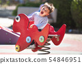 Cute happy baby boy with blond hair riding red spring rider or rocker on sunny summer day. 54846951