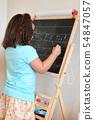 Cute girl schoolgirl writing on chalkboard. concept of education and school life. 54847057