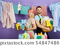 positive young couple with baskets full of dirty clothes 54847486