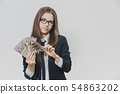 Concentrated young business woman is counting a pile of money, isolated on white background. Girl is 54863202