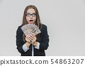 Shocked, excited young business woman is showing a pile of money, isolated on white background. Girl 54863207