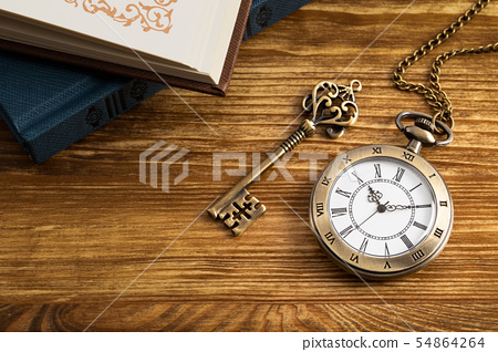 Vintage pocket watch clock with key and book on 54864264