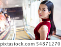 Beautiful young asian woman in red dress going 54871270