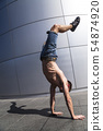 Young man in denim shorts breakdancing outdoor 54874920