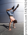 Young man in denim shorts breakdancing outdoor 54874924