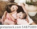 Sweet little sisters hugging on stack of hay. 54875889