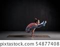 woman practices yoga hand balance asana titibhasana or firefly pose 54877408