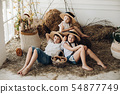 Cute sisters and brother in hay hats resting on 54877749