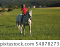 Young girl on roan horse walk on meadow in late 54878273