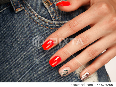 Bright neon red manicure on female hands on the background of jeans. Nail design. Beauty hands. 54879260