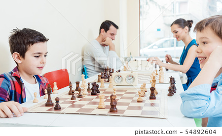 Family playing chess in tournament room 54892604