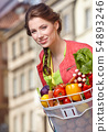 Pretty spring  woman with bicycle and groceries in 54893246