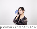Smiling young woman having a conversation on a smartphone in front of a white background 54893732