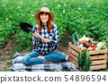 Beautiful female farmer with a shovel on a blanket near fresh organic vegetables in a wooden box 54896594