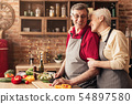 Lovely seniors embracing at kitchen, cutting vegetables for salad 54897580