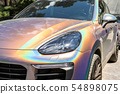 Close-up LED headlight expensive car part with exclusive iridescent painting. Vehicle covered with 54898075