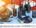 Many portable radio transceivers on table at technology exhibition. Different walkie-talkie radio 54898121