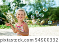 Little happy girl playing soap bubbles on the topical beach 54900332