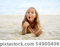Surprised cute little blonde girl relax on the beach on summer holiday 54900406