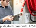 Asian technician checking fire hose reel 54901250