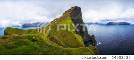 Small lighthouse located near huge cliffs on island of Kalsoy, Faroe Islands 54902389